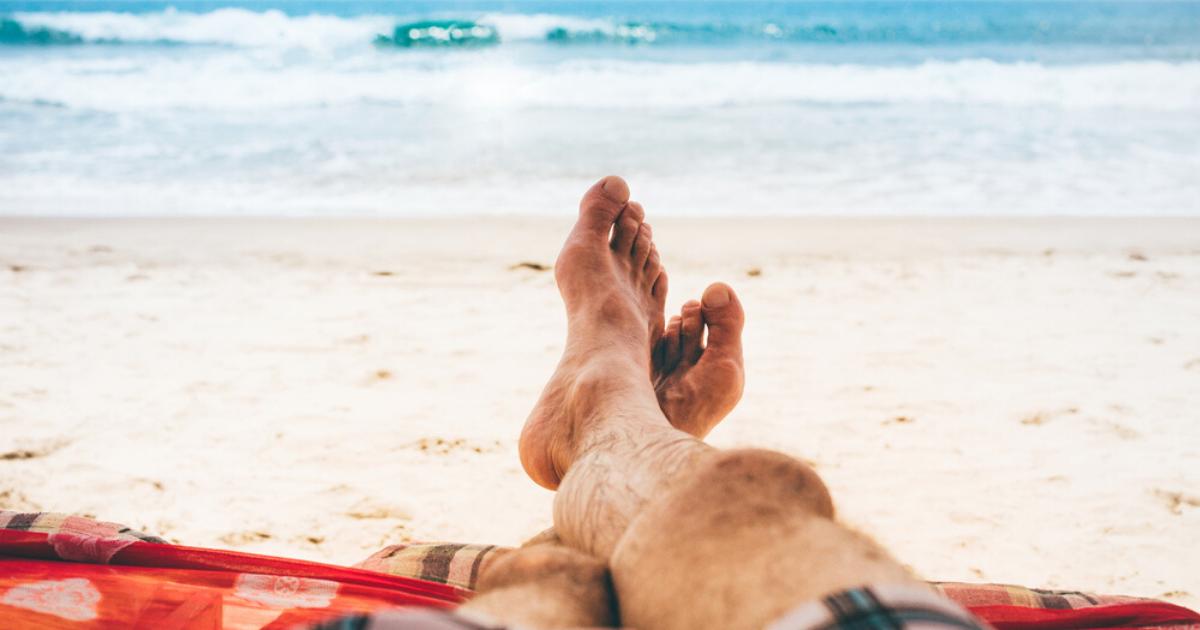 Athletes foot treatment man happy on beach shore with healthy feet happy
