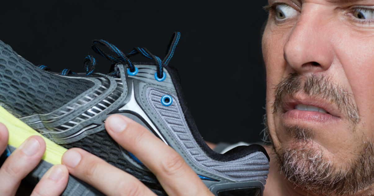 Man disgusted by his sweaty feet and smelly shoes wondering how to keep his feet dry