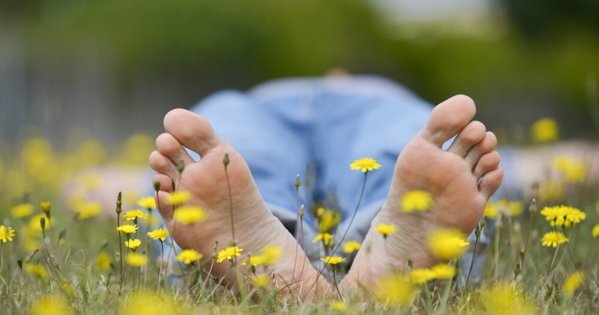man happily happily lying down on grass after fixing sweaty feet problem