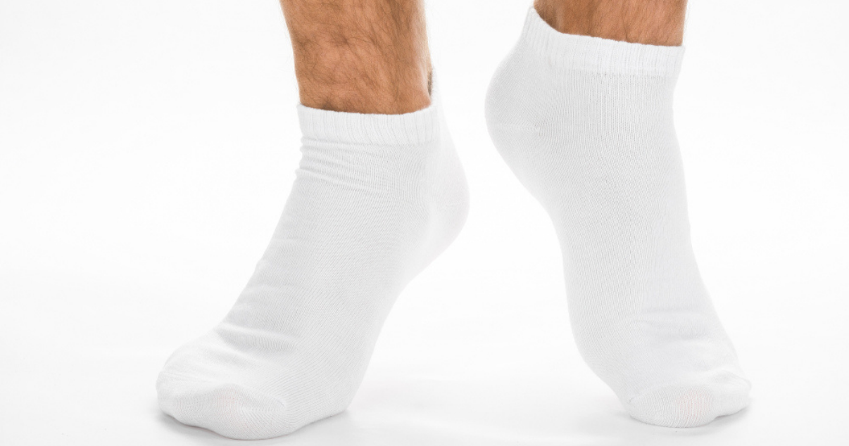 man changing into a fresh pair of cotton socks to prevent athletes foot