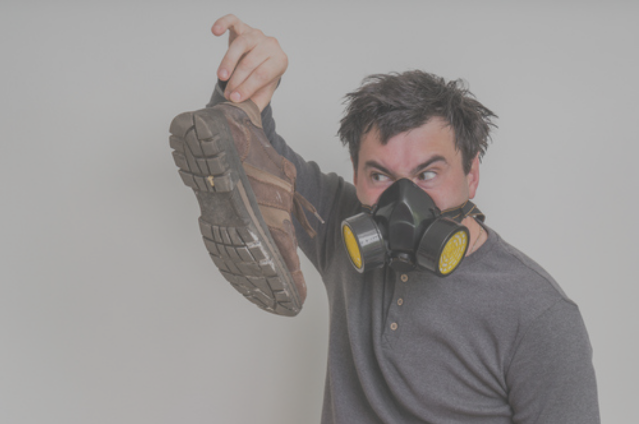 Man holding shoes with strong athlete's foot smell