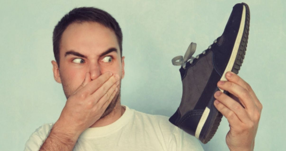 Man smelling shoes with a strong athletes foot smell