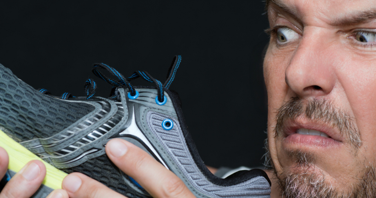 Disgusted man smelling his running shoes wondering if he has an ahletes foot infection