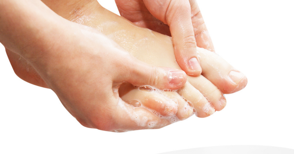 Woman washing her feet as she remembers the tips for preventing athletes foot infection