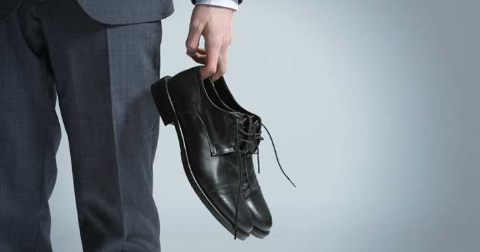 man taking off tight fitting shoes to prevent athletes foot