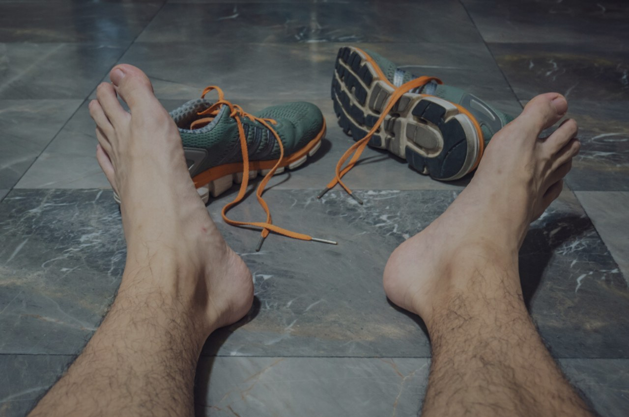 man taking sweaty shoes off wondering which athletes foot treatment is best for him